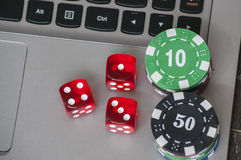 Gambling chips and red dice on laptop keyboard background Stock Image