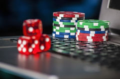 Gambling chips and red dice on laptop keyboard background Stock Images