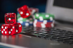 Gambling chips and red dice on laptop keyboard background Royalty Free Stock Images