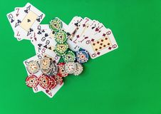 Gambling chips stack and playing cards on green table. stock images