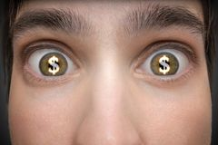 Gambling concept. Young man has dollar signs in his eyes Stock Photo