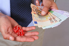 Gambling connect. Man winner holding money and gambling dice. Business Risk and Success Stock Photo