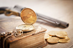 Gambling and crime concept with gold coins and gun Royalty Free Stock Image