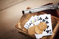 Gambling and crime concept with gun, cards and golden coins Royalty Free Stock Images