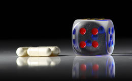 Gambling and drugs. A single die sitting next to some pills, good concept for danger or addiction Stock Photo