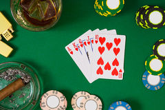 Gambling, fortune and entertainment concept - close up of casino chips, whisky glass, playing cards and cigar on green Royalty Free Stock Images