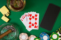 Gambling, fortune and entertainment concept - close up of casino chips, whisky glass, playing cards and cigar on green Stock Photos