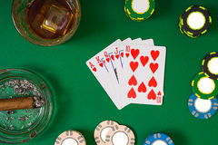 Gambling, fortune and entertainment concept - close up of casino chips, whisky glass, playing cards and cigar on green royalty free stock photography