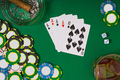 Gambling, fortune and entertainment concept - close up of casino chips, whisky glass, playing cards and cigar on green Stock Photography
