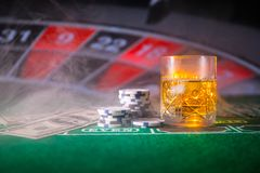 Gambling, fortune, game and entertainment concept - close up of casino chips and whisky glass on table. Selective focus royalty free stock photos