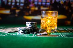gambling, fortune, game and entertainment concept - close up of casino chips and whisky glass on table royalty free stock image