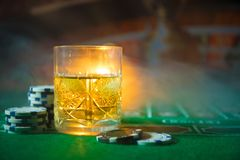 Gambling, fortune, game and entertainment concept - close up of casino chips and whisky glass on table. Selective focus royalty free stock image