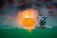 Gambling, fortune, game and entertainment concept - close up of casino chips and whisky glass on table. Selective focus royalty free stock photo