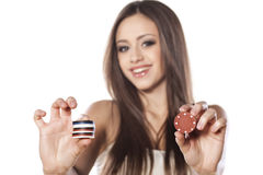 Gambling girl. Smiling girl holding gambling chips in her hands on white background royalty free stock photo