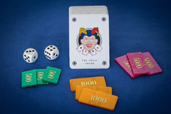 Gambling. Jolly Joker with fishes and dice on blue table Stock Photos