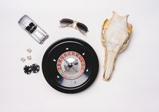 Gambling life. Still life of a gambler. Background of a casino table with roulette wheel, sunglasses, Poker chips, dices, a model car and a skull. Ready to play royalty free stock photography