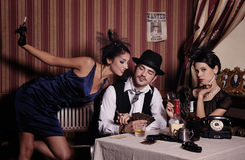 Gambling mafia type with cigarette, playing poker. Gambling mafia type with cigarette, playing poker, picture in retro style. Focus on  man Stock Image