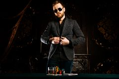 Gambling mature man. A wealthy mature man playing poker in a casino. Gambling, playing cards and roulette stock photos