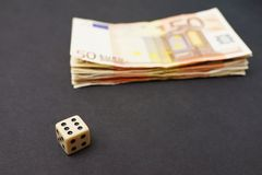 Gambling money. Dice lying infront of a stash of 50 euro banknotes, for concepts like gambling, risk, luck and investments - focus is on the dice Royalty Free Stock Photography