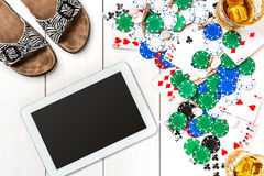 Gambling. Poker chips, cards and the dice nearby tablet on wooden table. Top view. Copyspace. Poker Stock Photos
