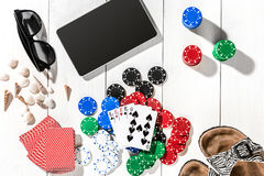 Gambling. Poker chips, cards and the dice nearby tablet on wooden table. Top view. Copyspace. Poker Royalty Free Stock Photography