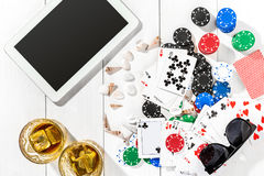 Gambling. Poker chips, cards and the dice nearby tablet on wooden table. Top view. Copyspace. Poker Stock Image