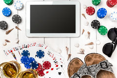 Gambling. Poker chips, cards and the dice nearby tablet on wooden table. Top view. Copyspace. Poker Stock Images