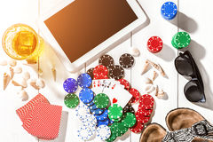 Gambling. Poker chips, cards and the dice nearby tablet on wooden table. Top view. Copyspace. Poker Royalty Free Stock Image