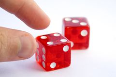 Gambling Problem?. A man goes to pick up dice after rolling a 7. Should he do it? On the side of the dice it says Las Vegas stock photography