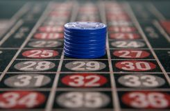 Gambling on a roulette table with blue chips. Macro Stock Image