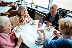 Gambling. Senior friends gathered in cafe for card play stock images