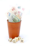 Gambling in South Africa. An old used brown leather dice cup with South African money (Rand) inside and dice lying around. Image isolated on white studio Stock Image