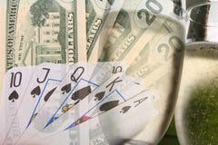 Gambling spree - Dollars. Pile of twenty dollar notes, poker royal flush and  2 champagne flutes suggesting gambling vacation Royalty Free Stock Photo