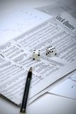 Gambling on the stock market. Rolling the dice on the stock market, with analysis sheets and a pen royalty free stock image