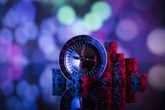 Gambling theme. Place for text and typography. Roulette wheel and stack of poker chips on glass table. Colorful bokeh background royalty free stock image