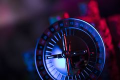 Gambling theme. Place for text and typography. Roulette wheel and stack of poker chips on glass table. Colorful bokeh background royalty free stock photo