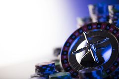 Gambling theme. Place for typography. Roulette and poker chips on blue bokeh background. Place for text royalty free stock image