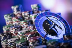 Gambling theme. Place for typography. Roulette and poker chips on blue bokeh background. Place for text stock photos