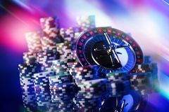 Gambling theme. Place for typography. Roulette and poker chips on blue bokeh background. Place for text stock photo