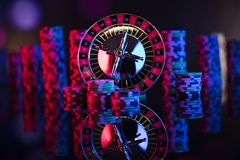 Gambling theme. Place for typography. Roulette and poker chips on color bokeh background. Place for text royalty free stock photos