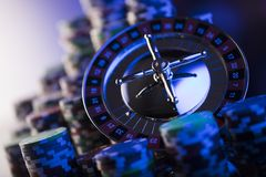 Gambling theme. Place for typography. Roulette and poker chips on color bokeh background. Place for text royalty free stock images