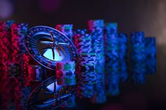 Gambling theme. Place for typography. Roulette and poker chips on color bokeh background. Place for text stock photography