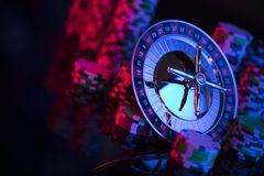 Gambling theme. Place for typography. Roulette and poker chips on color bokeh background. Place for text royalty free stock photography