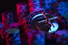 Gambling theme. Place for typography. Roulette and poker chips on color bokeh background. Place for text stock images