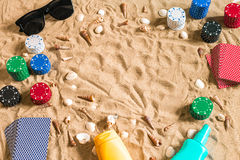 Gambling on vacation concept - white sand with seashells , colored poker chips and cards. Top view Stock Photo