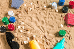 Gambling on vacation concept - white sand with seashells , colored poker chips and cards. Top view Royalty Free Stock Photos