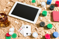 Gambling on vacation concept - white sand with seashells , colored poker chips and cards. Top view. Copy space. Summer Royalty Free Stock Photography