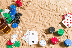 Gambling on vacation concept - white sand with seashells , colored poker chips and cards. Top view. Copy space. Summer Stock Photo