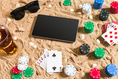 Gambling on vacation concept - white sand with seashells , colored poker chips and cards. Top view. Copy space. Summer Royalty Free Stock Image