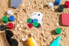 Gambling on vacation concept - white sand with seashells , colored poker chips and cards. Top view. Copy space. Summer Royalty Free Stock Images